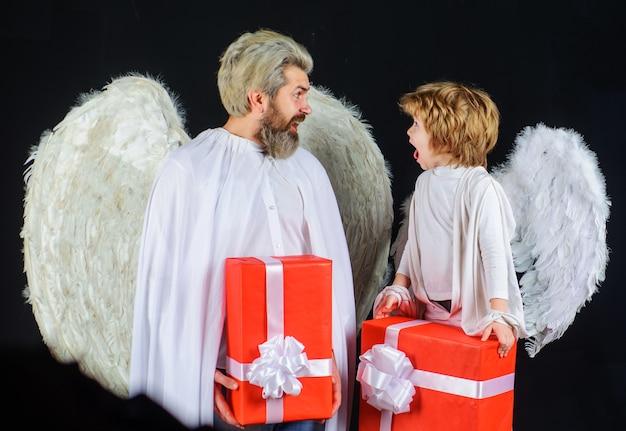 Valentinstag engel. vater und sohn engel mit roter gabe. glückliche mannfamilie mit flügeln.