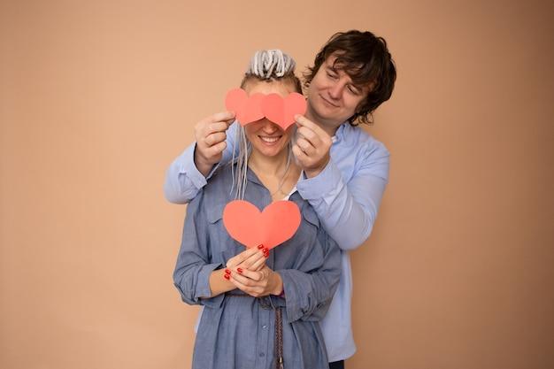 Valentinstag feiern. paar mit roten herz-valentinsgrüßen in den händen auf beigem hintergrund
