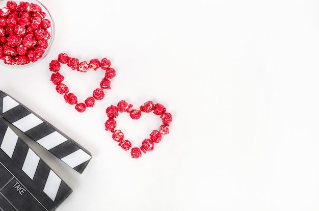 Valentinstag filmkonzept. clapperboard mit herzen aus rotem karamellpopcorn mit kopienraum auf weißem hintergrund.
