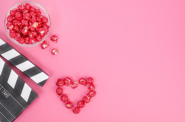 Valentinstag filmkonzept. filmklappe mit rotem karamellpopcornherz mit kopienraum auf rosa hintergrund.