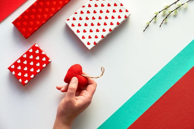 Valentinstag flach lag, draufsicht auf weiß. geometrischer hintergrund mit weidenkätzchen. geschenkboxen und weiches textilspielzeugherz in der hand. geometrischer zweifarbiger geteilter papierhintergrund.