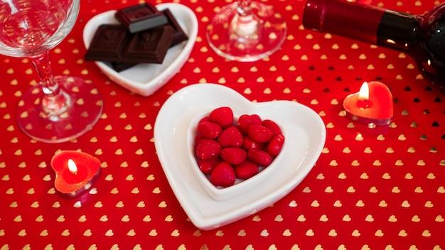 Valentinstag. flasche wein, gläser, rote rosen, kerzen - roter hintergrund. liebesdinner-konzept