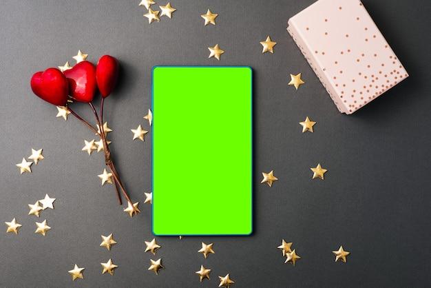 Valentinstag, foto von roten herzen mit geschenk und im mittleren grünen bildschirm auf tablette