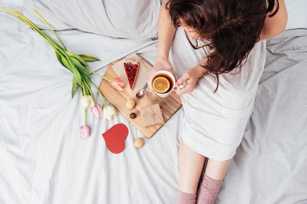 Valentinstag. frühstück, ein geschenk und blumen für das mädchen, das sie lieben. mädchen im bett mit blumen am 14. februar.
