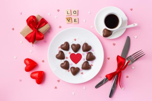 Valentinstag frühstück. herz gemacht von den pralinen, vom geschenk mit einem roten bogen und vom cu des kaffees auf rosa