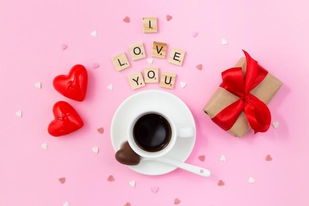 Valentinstag frühstück. tasse kaffee mit pralinen, geschenkbox mit einem roten bogen und kerzen auf rosa