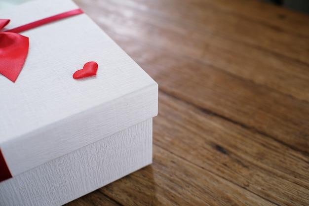 Valentinstag geschenk. geschenkbox und rotes band für romantische paare.
