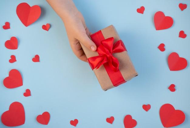 Valentinstag. geschenk in der hand, eine liebeserklärung, eine schachtel mit einem roten band. ansicht von oben
