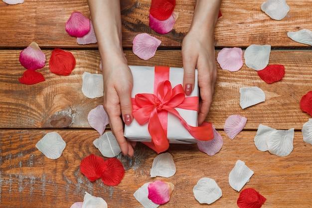 Valentinstag geschenk und weibliche hände auf holz mit blütenblättern