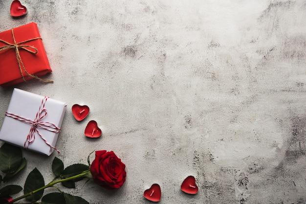 Valentinstag, geschenkbox aus kraftpapier mit einem band, rose und kerzen auf grauem hintergrund
