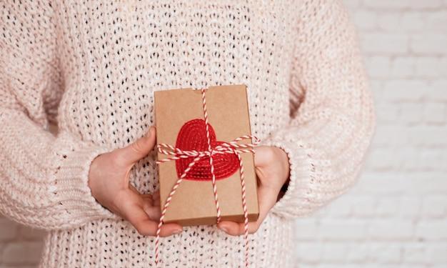 Valentinstag geschenkbox mit rotem herzen in den händen des mädchens