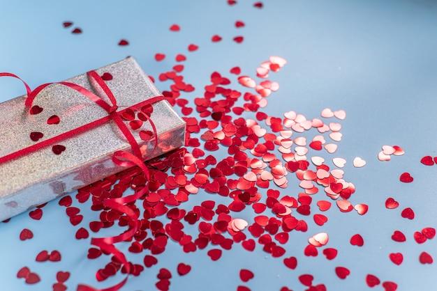 Valentinstag-geschenkbox mit rotem herzförmigem glitzer auf blauem hintergrund