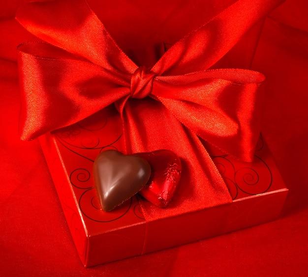 Valentinstag. geschenkbox und süßigkeiten in form eines herzens auf rotem grund