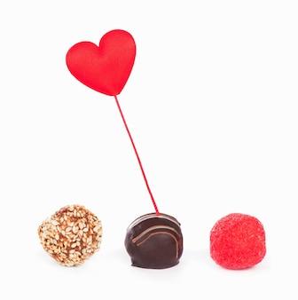 Valentinstag. geschenkbox und süßigkeiten in form eines herzens auf weißem hintergrund