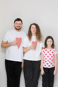 Valentinstag. glückliche familie, mama, papa und kleine tochter in weißen t-shirts, die handgemachte rote herzen in ihren händen halten, die kamera betrachten