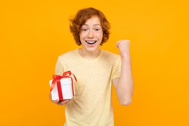 Valentinstag . glücklicher rothaariger jugendlicher mit einem geschenk in seinen händen auf einem gelb