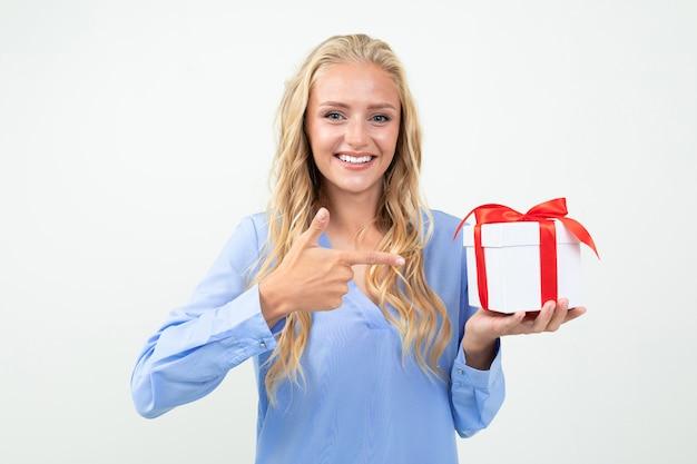 Valentinstag . glückliches blondes mädchen, das ein geschenk in ihren händen auf einem weiß hält