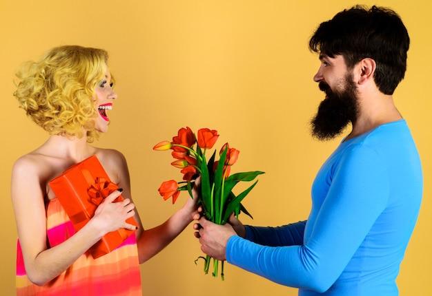 Valentinstag. glückliches paar mit geschenk und blumen. mann gibt frau blumen. urlaub, liebe, dating.