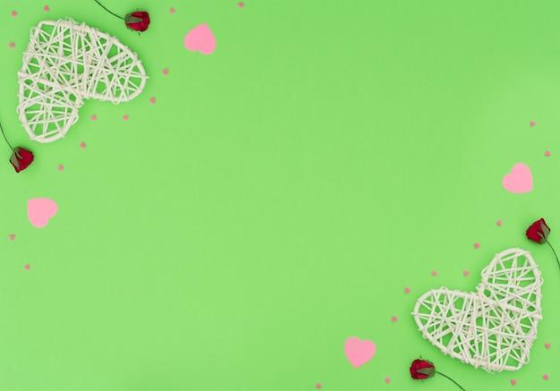 Valentinstag grün mit rattan und papierherzen, roten rosen und kleinen rosa herzen