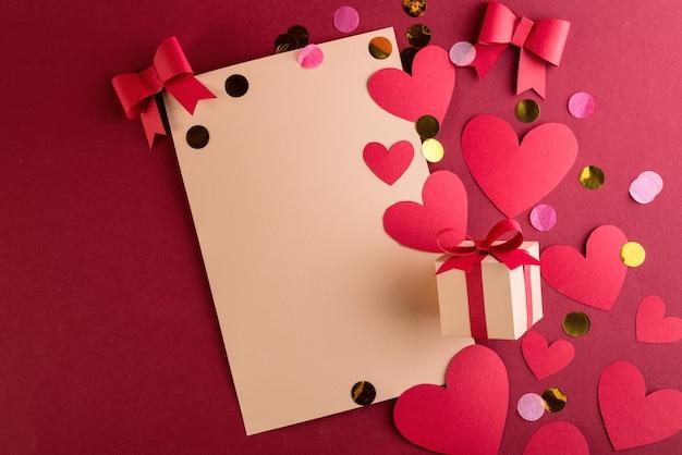 Valentinstag-grußkarte mit papierschnittband, schleife und vielen herzen