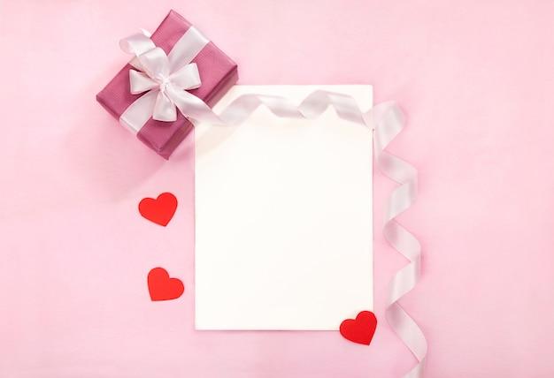 Valentinstag-grußkarte mit rosa geschenkbox, weißer schleife, langem gebogenem band und roten papierherzen. gesamtansicht, platz für text