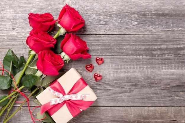 Valentinstag-grußkarte mit rotem rosenblumenstrauß und geschenkbox auf einem jahrgang auf grauem holztisch