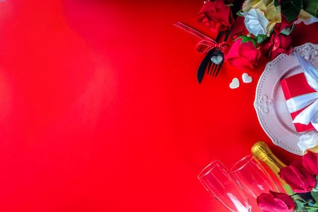 Valentinstag-grußkarte mit rotem rosenblumenstrauß, wein und geschenkbox auf rotem tisch. draufsicht mit platz für grüße. valentinstag hintergrund flach lag