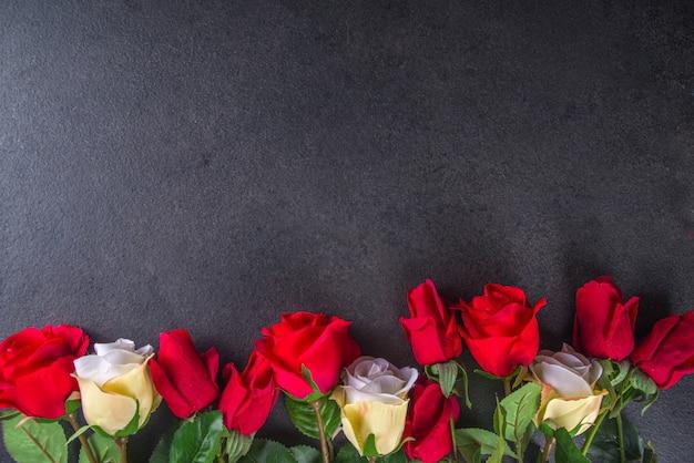 Valentinstag-grußkarte mit rotem rosenblumenstrauß, wein und geschenkbox auf schwarzem tischtisch. draufsicht mit platz für grüße