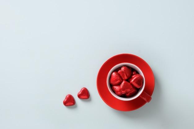 Valentinstag grußkarte mit roten herz süßigkeiten, geschenk und tasse auf blau.