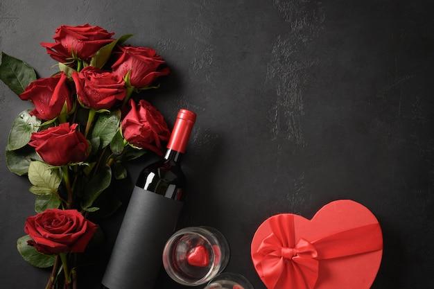 Valentinstag-grußkarte mit roten rosen und wein- und herzgeschenk auf schwarzem hintergrund mit kopienraum.