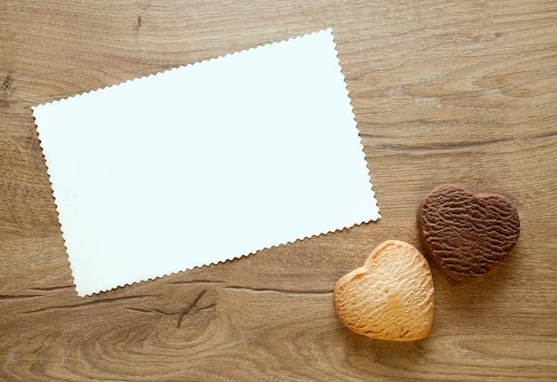 Valentinstag-grußkarte mit zwei gebackenen herzförmigen keksen auf hölzernem hintergrund.
