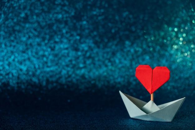 Valentinstag grußkarte. origami-boot mit herzfahne auf glitzerndem blauem hintergrund romantisches valentinstagkonzept mit raum für text.