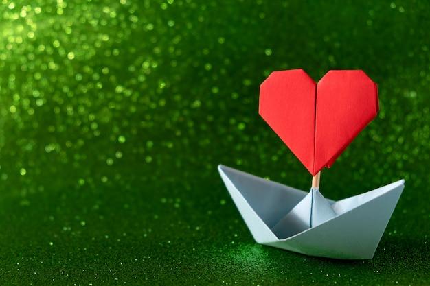 Valentinstag grußkarte. origami-boot mit herzfahne auf glitzerndem grünem hintergrund romantisches valentinstagkonzept mit raum für text.