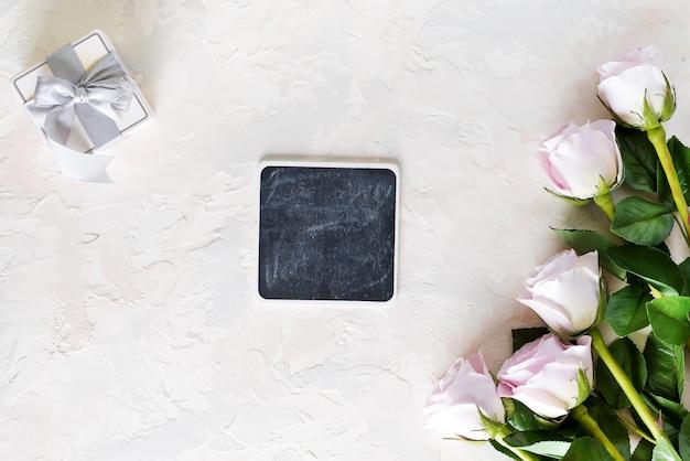 Valentinstag-grußkarte. rosa rosen und geschenkbox mit kleinen kreidebrettern auf hellem stein, draufsicht mit copyspace