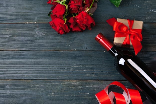 Valentinstag-grußkarte. rotrosenblumen, wein und geschenkbox auf holztisch.
