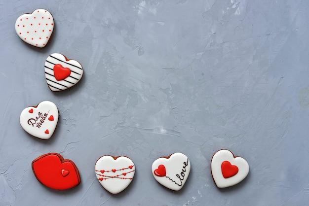Valentinstag hausgemachte kekse auf ultimate grey hintergrund, draufsicht. platz für text. köstlich und süß, bedeckt mit zuckerguss mit einer wunderschönen muster-lebkuchen-inschrift in russischer sprache - für sie