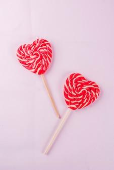 Valentinstag hellrosa hintergrund grußkarte konzept zwei rote herzen lutscher oder süße süßigkeiten auf stöcken