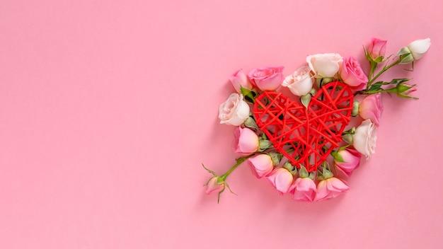 Valentinstag . herzform aus blumen. valentinstag hintergrund. rosen auf pastellrosahintergrund. flache lage, draufsicht, kopienraum.