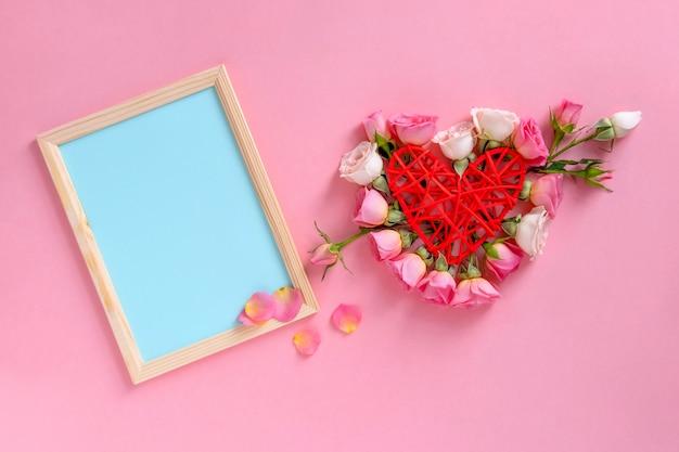Valentinstag . herzform aus blumen. valentinstag hintergrund. rosen auf pastellrosahintergrund.