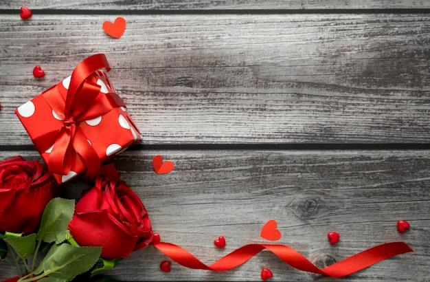 Valentinstag hintergrund. draufsicht von rose, geschenkbox, herzen und band auf holztisch mit copyspace für text.
