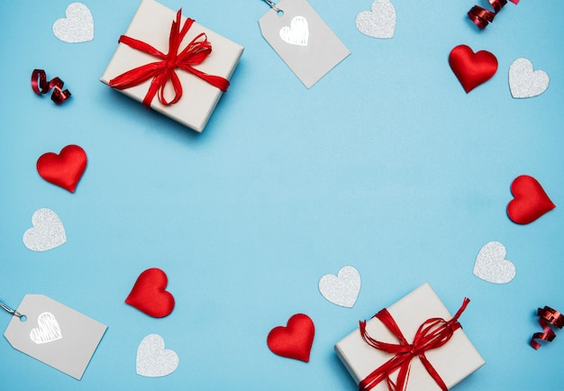 Valentinstag hintergrund. geschenke, konfetti auf pastellblauem hintergrund. valentinstag konzept. flache lage, draufsicht, kopierraum