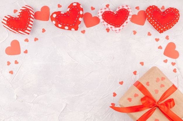 Valentinstag-hintergrund mit feld von den handgemachten textil- und konfetti-herzen