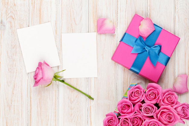 Valentinstag hintergrund mit geschenkbox voller rosa rosen und zwei leeren fotorahmen