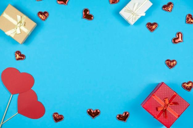 Valentinstag hintergrund mit rahmen mit geschenkboxen und roten herzen auf blauem hintergrund. draufsicht. flache lage, textraum