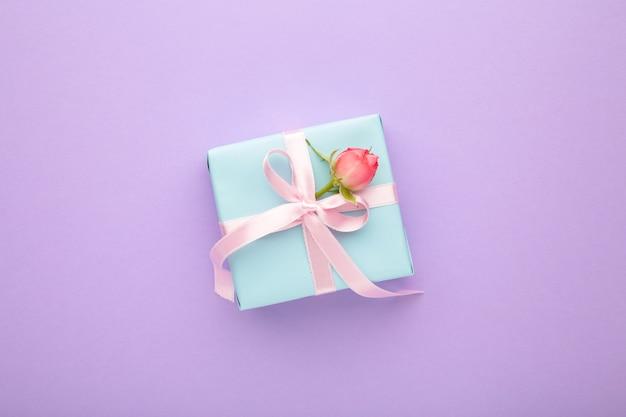 Valentinstag hintergrund mit rosa rose und geschenkbox auf lila hintergrund. draufsicht mit kopierraum.