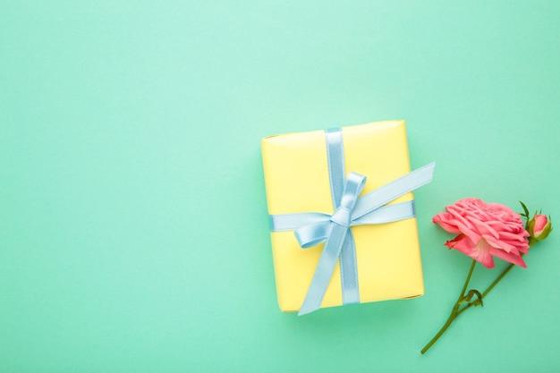Valentinstag hintergrund mit rosa rose und geschenkbox auf minze hintergrund. draufsicht mit kopierraum.