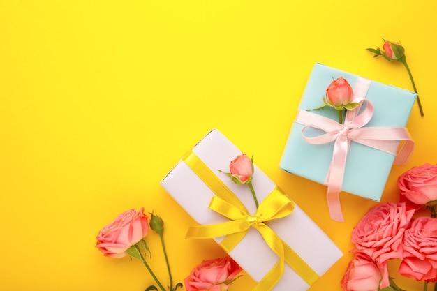 Valentinstag hintergrund mit rosa rosen und geschenkbox auf gelbem hintergrund. draufsicht mit kopierraum.