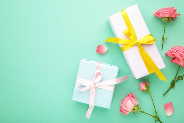 Valentinstag hintergrund mit rosa rosen und geschenkbox auf minze hintergrund. draufsicht mit kopierraum.