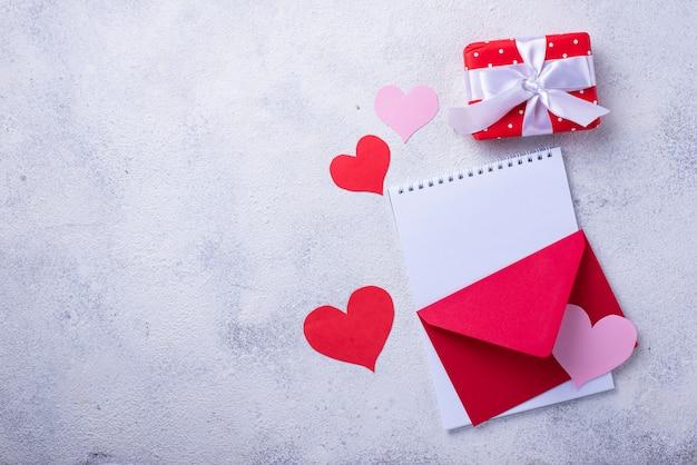 Valentinstag hintergrund mit umschlag, geschenkbox und grußkarte