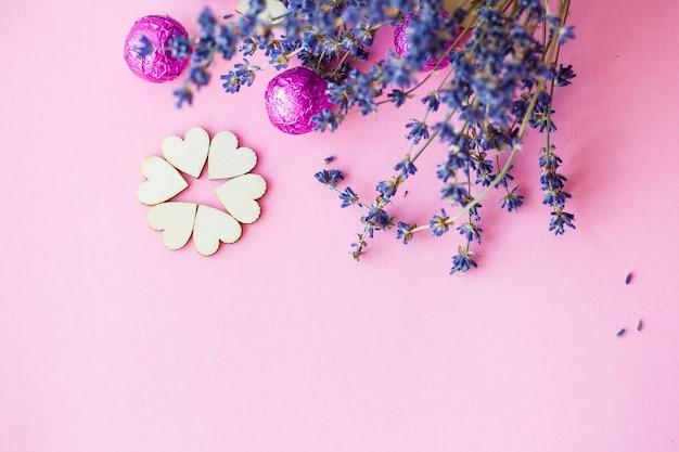 Valentinstag hintergrund. reihe von holzherzen auf rosa hintergrund, seitenansicht eines zweiges von trockenem lavendel. valentinstag-konzept. draufsicht, platz für beschriftung, werbung